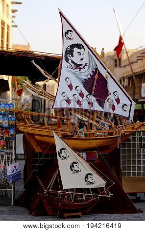 DOHA, QATAR - JULY 6, 2017: The sails of model dhows are emblazoned with flags and images of Qatari Emir Sheikh Tamim in the capital's Souq Waqif during the crisis between Qatar and its neighbours
