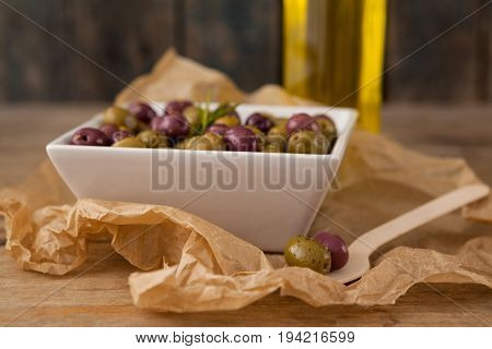 Close up of olives served in bowl by wooden spoon on wax paper