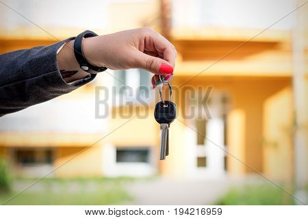 Concept Of Buying, Selling And Renting Housing. A Woman's Hand Holds The Keys To An Apartment Or A H