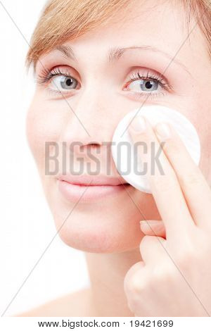 Female in bathroom claening face skin with batting cotton pads poster