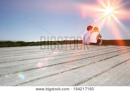 Rear view of young boy and girl sitting on boardwalk