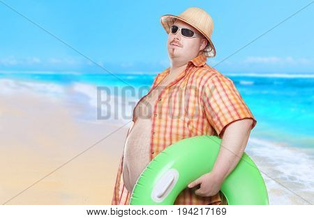 Obese man in shirt with green lifebuoy. Holidays on the beach. Funny lifeguard sending greeting from tropical paradise.