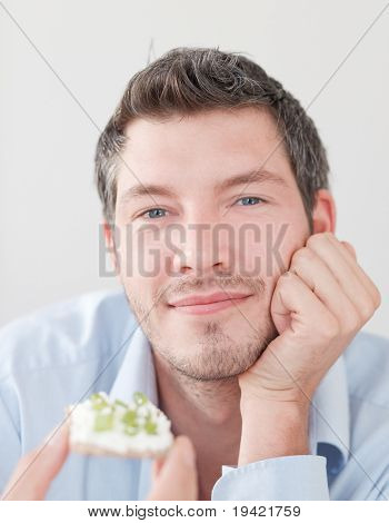 Happy man eating healthy crisp bread making a diet