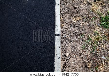 New asphalt concrete and concrete kerb on the road.
