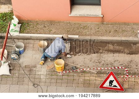 Bricklayer at work laying stone blocks of pavement.