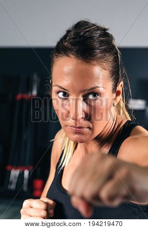 Closeup of beautiful woman training hard boxing in the gym