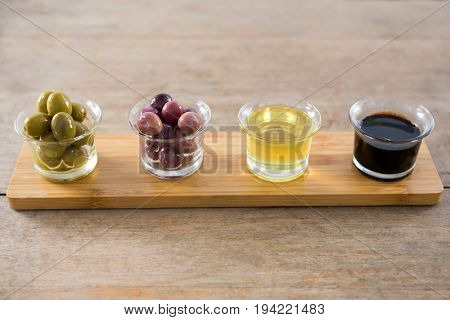 Close-up of marinated olives with olive oil and balsamic vinegar in glass container on a wooden tray