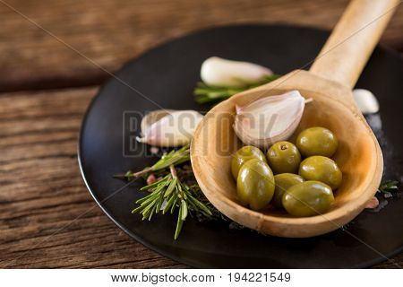 Close-up of green olives, rosemary and wooden ladle on table