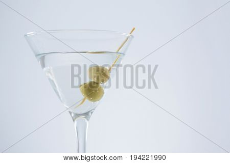 Close-up of cocktail martini with olives on table against white background