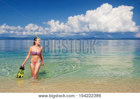 Happy woman after snorkeling with snorkel and mask coming out of the sea.