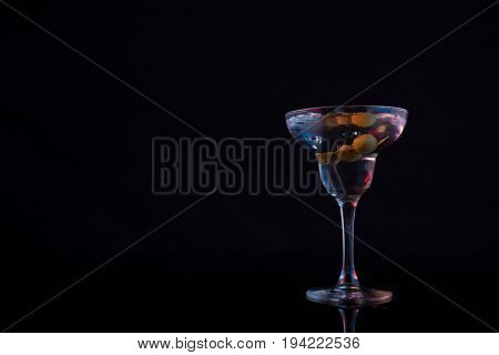 Close-up of cocktail martini with olives on table against black background