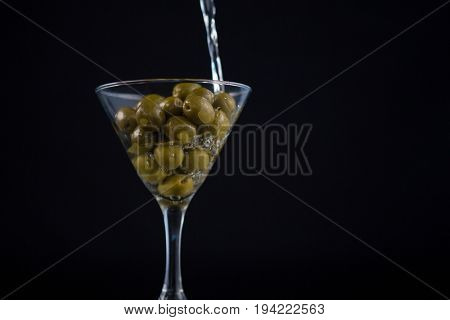Martini pouring into glass with olives against black background