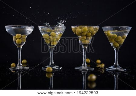 Close-up of olives splashing in to a cocktail martini with lime on table against black background