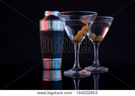 Close-up of cocktail martini with olives and shaker on table against black background