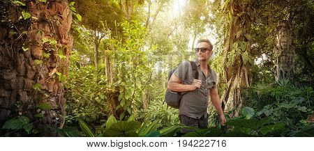 explorer- tourist with backpack studies ancient ruins in the Central America wild jungles. Concept travel and adventure.