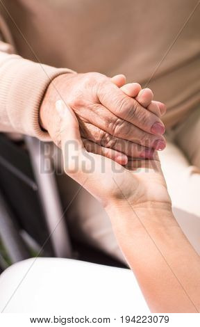 Close-up of caregiver holding her patient's hand
