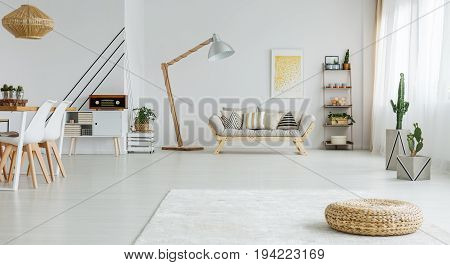 Cozy white living room with dining space and wooden sofa