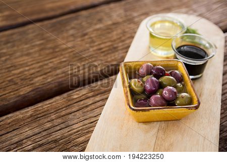 Close-up of marinated olive, rosemary with olive oil and balsamic vinegar on wooden tray