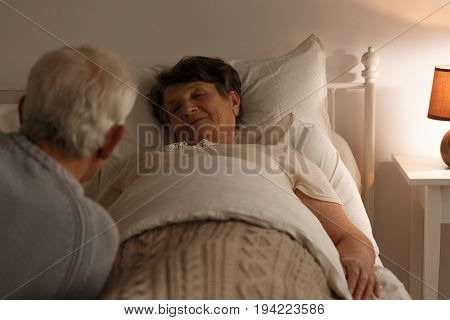 Senior woman laying in a bed and her husband sitting next to her