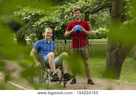Disabled man on wheelchair playing sport in the park with his friend