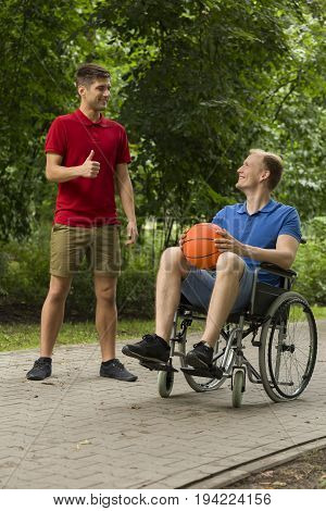 Handsome man and his friend on wheelchair holding a basketball
