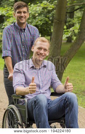 Disabled man on wheelchair spending time in a park with his brother