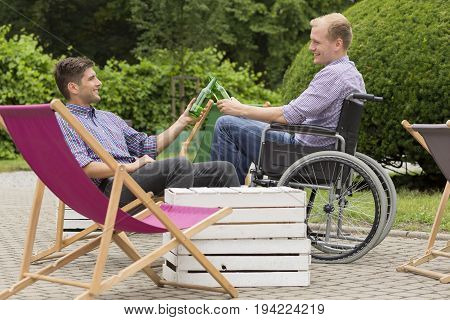 Disabled man on wheelchair and his friend drinking beer outdoors