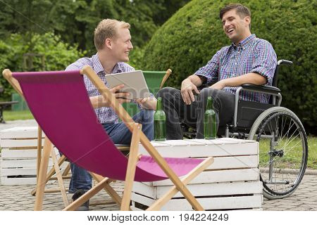 Positive man on wheelchair drinking beer with his friend outdoors