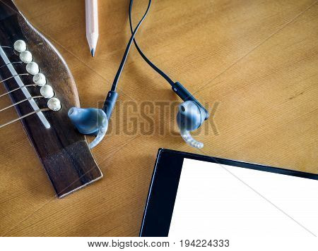 Close up shot of acoustic guitar with earphone and pencil