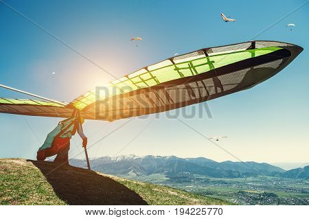 Hang-glider starting to fly over the mountains .