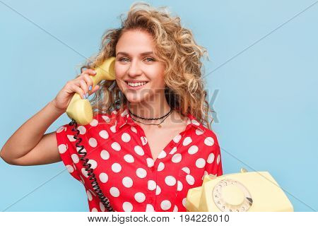 Blonde smiling woman in red shirt with white dots holding handset and telephone.