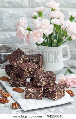 Paleo chocolate energy bars with rolled oats pecan nuts dates chia seeds and coconut flakes vertical