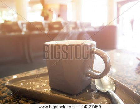 Hot cup of coffee on the table in sunlight