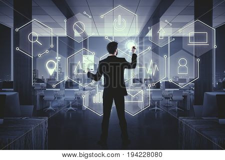 Back view of businessman drawing abstract digital business icons in dark office room. Touchscreen concept. Double exposure
