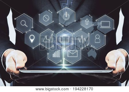 Businessman holding glowing tablet with abstract digital business icons hologram. Technology and innovation concept