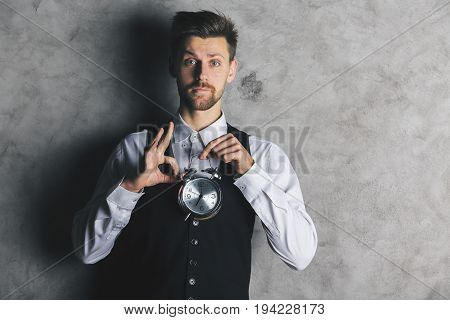 Attractive european businessman holding silver alarm clock and showing ok gesture on concrete background