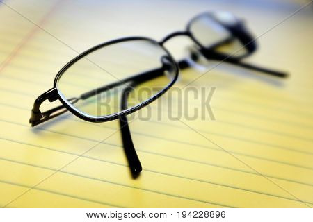 Glassed on yellow notepad in office