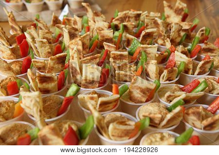 Small Appetizer hors d'oevres  in tiny cups with peta bread, peppers, vegetables, general party food