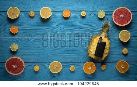 top view black vaporizer surrounded by citrus fruit: orange lemon Mandarin lime grapefruit
