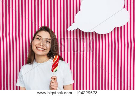 Smiling brunette girl wearing t-shirt holding ice-cream dreaming with word cloud against striped background.