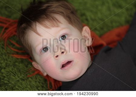 Little readhead boy is playing on the carpet