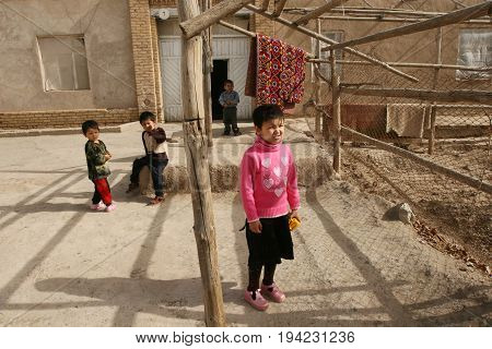 Khiva Uzbekistan - March 08 2009: Poverty in Uzbekistan. Children in the courtyard of the house play with themselves. No children's playgrounds. Everyday life