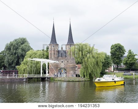 delft netherlands 30 june 2017: yellow boat waits for bridge to open near oostpoort in old dutch town of delft