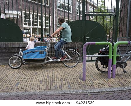 delft netherlands 30 june 2017: father waits with cargo bike at kindergarten in dutch town of delft