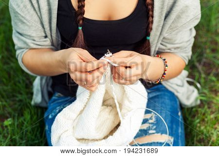 Close-up of a fashionable young woman knitting with knitting needles a white sweater on a bright green grass