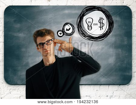 Handsome young businessman with hand put to head as a gun and thought bubble with lamp and dollar equation drawn on brick wall with chalkboard. Successful income ideas concept