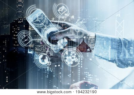 Man's hand holding smartphone with digital hologram. Abstract night city in the background. Communication concept. Double exposure