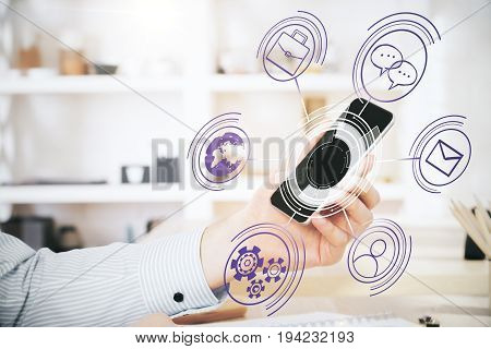 Side view of male hand holding smartphone with abstract digital projection above desktop in modern office. Innovation concept
