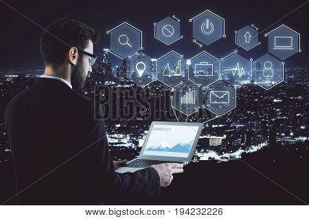 Side view of young businessman using laptop with glowing digital business projection on illuminated night city background. User media technology and analytics concept. Double exposure