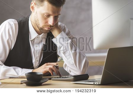 Portrait of attractive caucasian male worker accountant using calculator while sitting at office desk with devices and other items